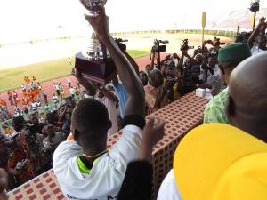 Le capitaine d'Abi Sport soulevant le trophée